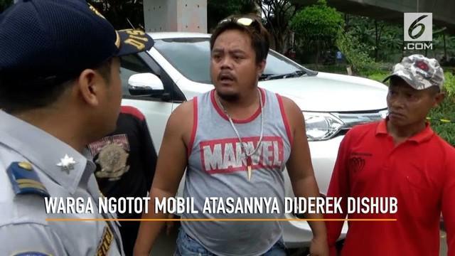 Seorang pria tak terima saat mobil atasannya diderek petugas Dinas Perhubungan hingga terjadi cekcok mulut.