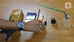 Petugas menata barang bukti saat rilis kasus narkoba yang menjerat artis peran Rio Reifan di Polres Metro Jakarta Pusat, Rabu (21/4/2021). Ditangkap pada Senin, 19 April 2021, ini merupakan kali keempat Rio Reifan berurusan dengan polisi karena kasus narkoba. (Liputan6com/Herman Zakharia)