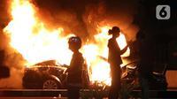 Sebuah mobil plat merah atau mobil dinas dibakar massa di kawasan Gondangdia, Jakarta, Kamis (8/10/2020). Unjuk rasa menentang disahkannya Omnibus Law UU Cipta Kerja berujung aksi anarkis merusak berbagai fasilitas umum. (Liputan6.com/Helmi Fithriansyah)