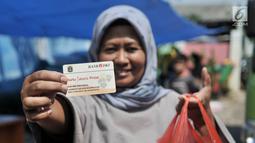 Warga menunjukkan KJP dan kebutuhan pokok yang dibeli dari Program Pangan Murah di RPTRA Utakara Beriman, Jakarta, Kamis (20/6/2019). Program tersebut juga bertujuan meningkatkan gizi warga pemegang Kartu Lansia Jakarta, PPSU, PHL, PJLP, UMP, serta penghuni Rusun Pemda. (merdeka.com/Iqbal S Nugroho)