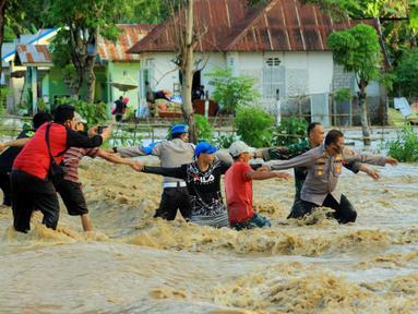 Petugas berusaha mengevakuasi warga saat banjir bandang  di Kabupaten Bone Bolango, Gorontalo (11/6/2020). Data sementara yang diterima dari BPBD Kabupaten Bone Bolango sekitar 1.078 kepala keluarga serta 5.407 jiwa terdampak banjir bandang. (Liputan.com/Arfandi Ibrahim)