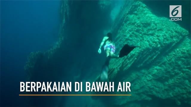 Salah satu freediver dunia melakukan percobaan menggunakan pakaian selam di bawah air.