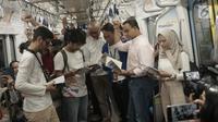 Gubernur DKI Anies Baswedan bersama masyarakat pengguna MRT tengah membaca buku yang disediakan disetiap stasiun MRT di Jakarta, Minggu (8/9/2019). Pemprov DKI Jakarta  meluncurkan ruang baca buku disetiap stasiun MRT untuk menumbuhkan minat baca masyarakat.(Liputan6.com/Angga Yuniar)