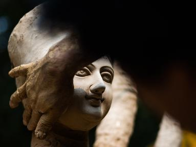 Seorang perajin membuat patung dewi Durga menjelang festival 'Durga Puja' di sebuah workshop di New Delhi, India, Rabu (14/10/2020). Durga Puja merupakan festival tahunan di Asia Selatan untuk memuja dewi Durga dari agama Hindu. (Photo by Jewel SAMAD / AFP)