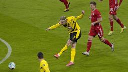 Dortmund sukses membuka keunggulan pada menit ke-2 melalui tembakan Erling Haaland dari luar kotak penalti. 7 menit berselang, Haaland kembali menjebol gawang Bayern Munchen. (Foto: AP/Pool/Guenter Schiffmann)