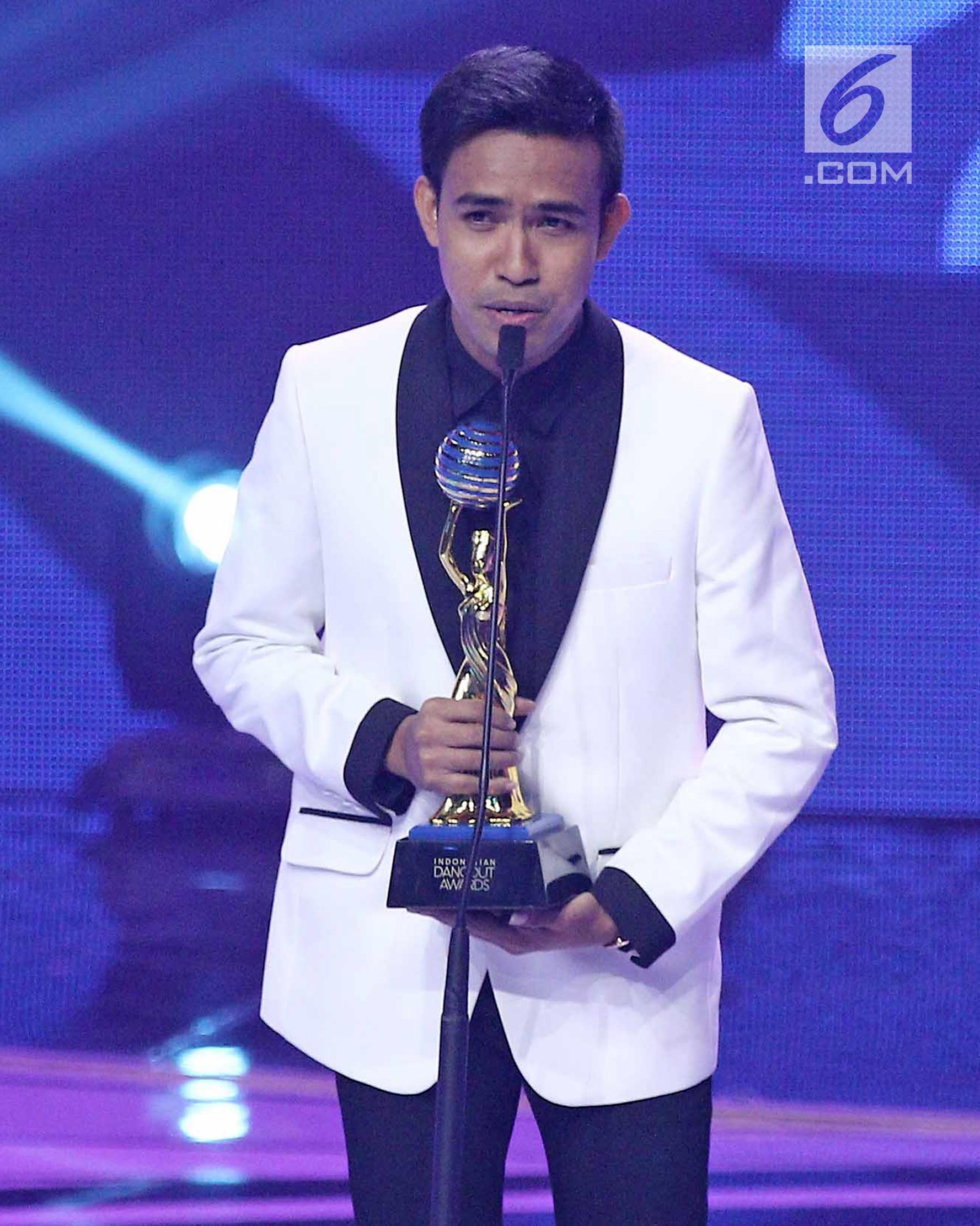 Fildan menerima piala untuk kategori penyanyi dangdut pendatang baru pria terbaik dalam ajang Indonesian Dangdut Awards 2017 di Studio 6 EMTEK CITY, Jakarta, Jumat (13/10). (Liputan6.com/Herman Zakharia)
