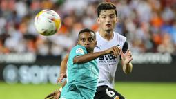 Penyerang Real Madrid, Rodrygo berebut bola dengan bek Valencia, Hugo Guillamon pada lanjutan La Liga di Stadion Mestalla, Senin (20/9/2021) dini hari WIB. Real Madrid menang 2-1 secara dramatis atas Valencia. (AP Photo/Alberto Saiz)