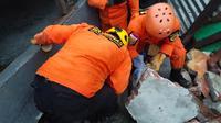 Tim penyelamat mencari korban yang terperangkap dalam sebuah bangunan runtuh di Mamuju, Sulawesi Barat, Indonesia, Jumat (15/1/2021). Gempa tidak berpotensi memicu tsunami. (HANDOUT/NATIONAL SEARCH AND RESCUE AGENCY/AFP)