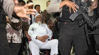 Terpidana kasus terorisme Abu Bakar Baasyir dikawal aparat kepolisian ketika tiba dengan kursi roda untuk menjalani operasi katarak di Jakarta, (29/02/2012). (AFP Photo/Romeo Gacad)