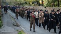 Sejumlah Reenactor Perang Dunia II mengenakan pakaian tentara berbaris saat mengikuti 'Railway in Wartime Event' yang ke 25 di Pickering, Inggris (15/10). (AFP Photo/Oli Scarff)