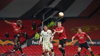 Gelandang Manchester United, Paul Pogba (kiri) menanduk bola yang berakhir sebagai gol kelima Manchester United ke gawang AS Roma dalam leg pertama semifinal Liga Europa di Old Trafford, Jumat (30/4/2021). Manchester United menang telak 6-2 atas AS Roma dalam laga ini. (Paul ELLIS / AFP)