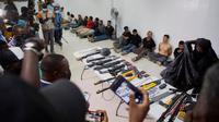 Tersangka dalam pembunuhan Presiden Haiti Jovenel Moise, bersama dengan senjata dan peralatan yang diduga mereka gunakan, ditunjukkan kepada media di Port-au-Prince pada 8 Juli 2021 (AP)