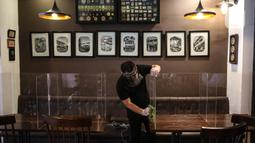 Pekerja membersihkan papan pelindung akrilik usai digunakan pengunjung di The Atjeh Connection Coffee and Resto, Jakarta, Senin (8/6/2020). Tempat ini siap menerapkan protokol kesehatan dalam menerapkan tatanan kehidupan baru atau 'new normal'. (Liputan6.com/Faizal Fanani)
