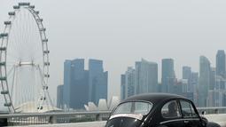 Sebuah kendaraan melintas saat kabut asap menyelimuti kota Singapura (15/9/2019). Polusi dari kebakaran hutan di Indonesia mendorong kualitas udara Singapura ke tingkat yang tidak sehat untuk pertama kalinya dalam tiga tahun. (AFP Photo/Roslan Rahman)