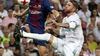 Aksi Barcelona, Ivan Rakitic (kiri) berebut bola dengan pemain Real Madrid, Sergio Ramos pada leg kedua Piala Super Spanyol di Santiago Bernabeu stadium (16/8/2017). Real menang 2-0. (AFP/Curto de La Torre)