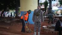 Petugas menghukum warga pelanggar Operasi Yustisi Pencegahan Covid-19 di kawasan Kampung Melayu, Jakarta Timur, Senin (16/11/2020). Operasi tersebut digelar guna menyadarkan masyarakat akan pentingnya penggunaan masker di tengah pandemi Covid-19. (Liputan6.com/Immanuel Antonius)