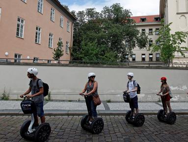 Sejumlah turis menggunakan segway untuk menikmati keindahan kota dan bangunan tua di pusat kota Praha, Ceko, Selasa (19/7). Segway adalah kendaraan personal listrik beroda 2 yang mampu menyeimbangkan sendiri. (REUTERS/David W Cerny)