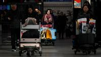 Penumpang mendorong troli barang bawaan saat tiba di Bandara Internasional Beijing pada Senin (20/1/2020). China berada di tengah-tengah kesibukan migrasi manusia tahunan ketika jutaan orang pulang ke kampung halaman mereka untuk menikmati libur Tahun Baru Imlek bersama keluarga. (WANG Zhao/AFP)