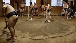 Para pegulat sumo menyapu tanah ring saat berlatih di Musashigawa Sumo Stable di Beppu, Jepang, Jumat (18/10/2019). Sumo adalah olahraga tradisional Jepang. (AP Photo/Aaron Favila)