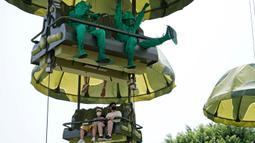 Pengunjung yang mengenakan masker menaiki wahana Toy Soldier Parachute Drop di Disneyland Hong Kong pada Jumat (25/9/2020). Setelah dibuka dan tutup kembali, Disneyland Hong Kong dibuka kembali untuk wisatawan. (AP Photo/Kin Cheung)