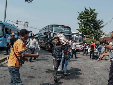 Petugas mengatur lalulintas di Terminal Kalideres, Jakarta, Kamis (30/5/2019). Menurut Badan Pengelola Transportasi Jabodetabek (BPTJ) puncak arus mudik di Terminal Kalideres diprediksi akhir pekan ini, mulai dari Jumat hingga Sabtu. (Liputan6.com/Faizal Fanani)
