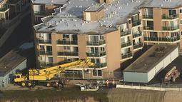 Pekerja merenovasi bangunan apartemen di atas bukit yang terkikis akibat badai El Nino di Pacifica Apartemen di Pacifica, California (26/1). Tiga Kompleks apartemen dikota ini  telah mengalami erosi akibat badai El Nino. (REUTERS/Noah Berger)