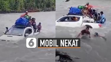 Aksi nekat dilakukan oleh sebuah mobil yang dinaiki beberapa orang diluar bak mobilnya menyebrangi sungai berarus deras.