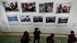 """Sejumlah pengunjung mengambil foto saat pameran karya fotografer Agence France-Presse (AFP) mengenai krisis migrasi di Eropa di pusat seni Bozar di Brussels (3/5). Pameran ini berjudul """"Puting a Face on the Invisibles. (AFP Photo/John Thys)"""
