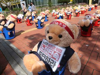 Boneka beruang teddy dipajang untuk memprotes kekerasan terhadap pedagang kaki lima ilegal, di depan kantor distrik Mapo di Seoul, Kamis (24/9/2020). Boneka beruang itu menggantikan pengunjuk rasa untuk menghindari pelanggaran larangan aksi dengan lebih dari 10 orang.  (AP Photo/Ahn Young-joon)