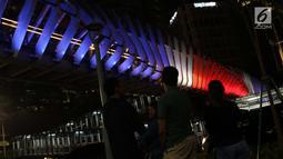 Warga melihat warna lampu seperti bendera Selandia Baru di JPO GBK, Jakarta, Minggu (17/3). Pencahayaan tematik ini telah dimulai sejak Jumat malam akan dipertahankan setiap malam hingga pagi selama sepekan ke depan.(Liputan6.com/Helmi Fithriansyah)