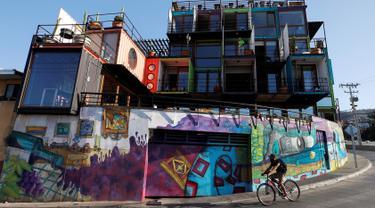 Pengendara sepeda melewati Hotel WineBox Valparaiso di Valparaiso, Chile, Senin (11/3). Hotel WineBox Valparaiso terbuat dari 25 kontainer bekas. (REUTERS/Rodrigo Garrido)