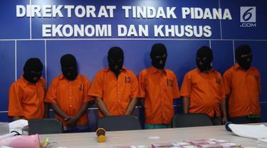 Petugas kepolisian menunjukkan tersangka peredaran uang palsu di Dirtipideksus Bareskirm Polri, Jakarta, Jumat (16/3). Polisi berhasil menggagalkan pembuatan dan peredaran uang palsu dengan menangkap enam tersangka. (Liputan6.com/Arya Manggala)