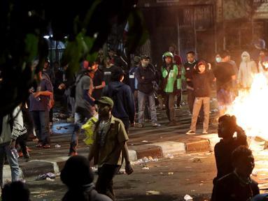 Massa berkumpul dan membakar kardus saat terjadi ricuh akibat unjuk rasa di sekitar jalan Pejompongan, Jakarta, Rabu (25/9/2019). Sebelumnya, unjuk rasa yang dilakukan pelajar STM bentrok dengan aparat kepolisian dibelakang Gedung DPR/MPR. (Liputan6.com/Helmi Fithriansyah)