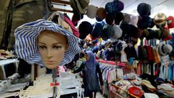Pengunjung melihat pakaian bekas impor di Pasar Baru Metro Atom, Jakarta, Jumat (6/12/2019). Di tengah ramainya produk pakaian baru baik lokal maupun internasional, pakaian bekas impor yang dijual di kios-kios pasar masih banyak peminatnya di berbagai kalangan. (merdeka.com/Imam Buhori)