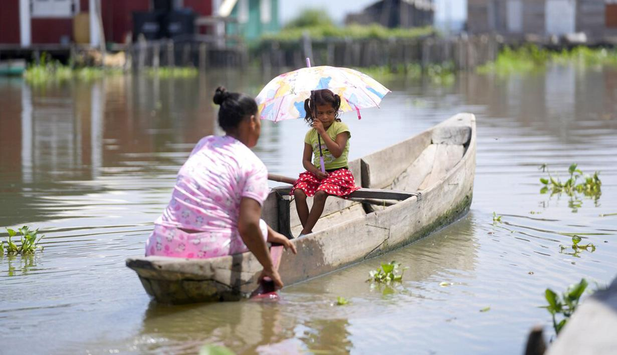 Seorang wanita mendayung sampan bersama putrinya di Cienaga Grande de Santa Marta, Nueva Venecia, Kolombia, 12 Oktober 2021. Sekitar 400 keluarga tinggal di rumah panggung di Cienaga Grande. (AP Photo/Fernando Vergara)