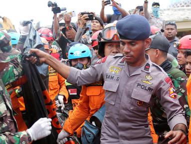 Tim SAR mengevakuasi jenazah korban gempa dari reruntuhan Masjid Jamiul Jamaah di Bangsal, Lombok Utara, Rabu (8/8). Berdasarkan kesaksian warga, diduga puluhan korban yang sedang melaksanakan pengajian tertimbun bangunan masjid. (AP/Tatan Syuflana)