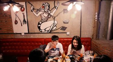 Pengunjung menikmati hidangan di restoran Ke'er di Beijing, China (26/5). Restoran bertema seks ini menyajikan menu hidangan seafood yang disajikan di atas piring dan gelas berbentuk payudara dan alat kelamin pria. (REUTERS/Kim Kyung-Hoon)