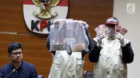 Petugas KPK melihat barang bukti uang hasil OTT di Gedung KPK, Jakarta, Sabtu (26/6/2019). Dalam OTT tersebut, KPK menyita uang 20.874 dolar Singapura, 700 USD dan Rp 200 juta dari lima tersangka. (Liputan6.com/Helmi Fithriansyah)