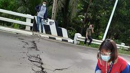 Relawan melihat retakan di jalan setelah gempa melanda Cataingan, Filipina tengah (18/8/2020). Badan seismologi Filipina menyatakan tidak ada potensi tsunami yang dipicu oleh gempa ini, namun warga diperingatkan akan adanya gempa susulan. (John Mark Lalaguna/Philippine National Red Cross via AP)