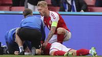 Gelandang Denmark, Christian Eriksen tergeletak di tanah setelah pingsan pada laga Denmark vs Finlandia di Grup B Euro 2020 di Parken Stadium, Copenhagen, Sabtu (12/6/2021). Laga dihentikan jelang berakhirnya babak pertama setelah Christian Eriksen pingsan. (Friedemann Vogel/Pool via AP)