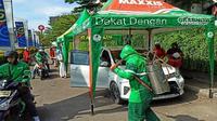 Aplikator Grab Cirebon melakukan penyemprotan cairan disinfektan kepada mitra baik roda dua maupun roda empat ditengah pandemi covid-19. Foto (Liputan6.com / Panji Prayitno)