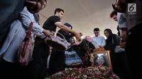 Putra kedua Ahmad Albar, Fachri Albar dan kerabat menaburkan bunga ke makam almarhum Faldy Albar di TPU Tanah Kusir, Jakarta, Kamis (30/8). Diketahui, Faldy Albar meninggal pada usia 36 tahun di Rumah Sakit Abdi Waluyo. (Liputan6.com/Faizal Fanani)
