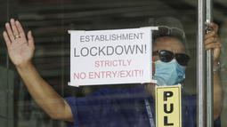 Seorang petugas keamanan berdiri di samping tanda di Malate Bayview Mansion yang dikunci karena jumlah kasus COVID-19 di Manila, Filipina (11/3/2021). Wali Kota Manila Isko Moreno mengatakan polisi tidak akan mengizinkan orang masuk dan keluar dari rumah mereka. (AP Photo/Aaron Favila)