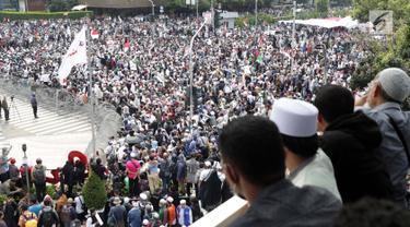 Warga melihat kerumunan peserta aksi massa Gerakan Nasional Kedaulatan Rakyat yang melakukan unjuk rasa di perempatan dekat Gedung Bawaslu, Jakarta, Rabu (22/5/2019). Dalam aksinya, mereka meminta Bawaslu memeriksa kembali hasil Pemilu 2019. (Liputan6.com/Helmi Fithriansyah)