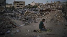 Seorang pria Palestina berdoa di samping puing-puing rumah keluarganya yang hancur karena serangan udara Israel di Beit Lahia, Jalur Gaza, Jumat (4/6/2021). Gencatan senjata yang mengakhiri perang 11 hari antara Hamas dan Israel telah lama dilakukan. (AP Photo/Felipe Dana)