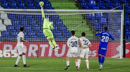 Penjaga gawang Real Madrid Thibaut Courtois melakukan penyelamatan saat melawan Getafe pada pertandingan Liga Spanyol di Stadion Alfonso Perez, Getafe, Spanyol, Minggu (18/42021). Pertandingan berakhir dengan skor 0-0. (AP Photo/Manu Fernandez)