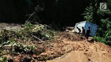 Sebuah truk terjebak longsor di ruas Ciwidey-Cidaun, Kabupaten Cianjur, Jawa Barat (27/4). Terdapat tiga titik lokasi longsor, yaitu di Kampung Cipandak, Desa Wangun Jaya, Kecamatan Naringgul, Kabupaten Cianjur. (Liputan6.com/Ahmad Sudarno)