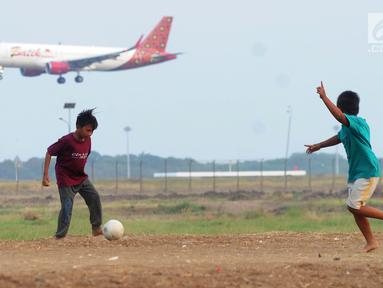 Anak-anak bermain bola di kawasan proyek perluasan landasan pacu atau Runway 3A Bandara Soekarno-Hatta (Soetta), Rawa Bokor, Tangerang, Banten, Selasa (2/7/2019). Mereka memanfaatkan lahan kosong yang belum dikerjakan pihak kontraktor untuk bermain bola. (merdeka.com/Arie Basuki)
