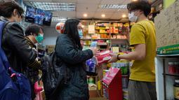 Orang-orang dengan mengenakan masker antre untuk membeli kertas tisu di apotek di Hong Kong, Kamis (6/2/2020). Warga Hong Kong yang sedang waspada virus corona dilanda kepanikan setelah muncul gosip bahwa China akan berhenti memproduksi kertas toilet selama dua pekan mendatang. (AP/Vincent Yu)