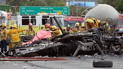 Sejumlah petugas mengevakuasi bangkai truk yang telah hangus usai terjadi tabrakan antara dua truk besar di utara pusat kota Los Angeles (25/4). Kecelakaan ini juga membuat kemacetan panjang di wilayah tersebut. (AP Photo/Reed Saxon)